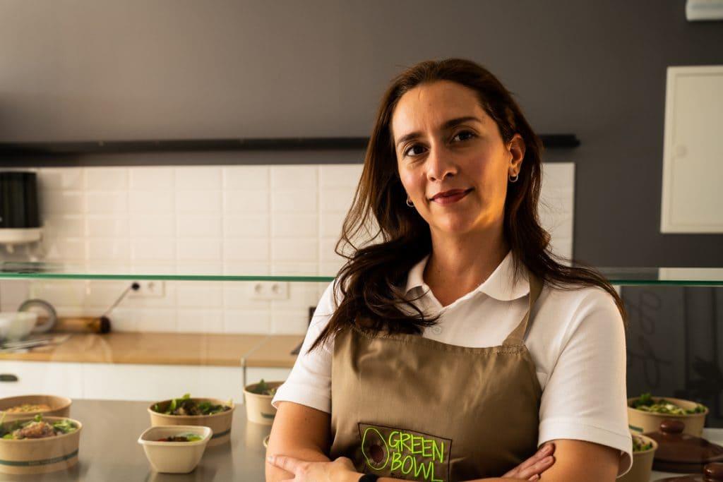 Mujer de cabello largo sonriendo con blusa blanca y delantal café en la cocina